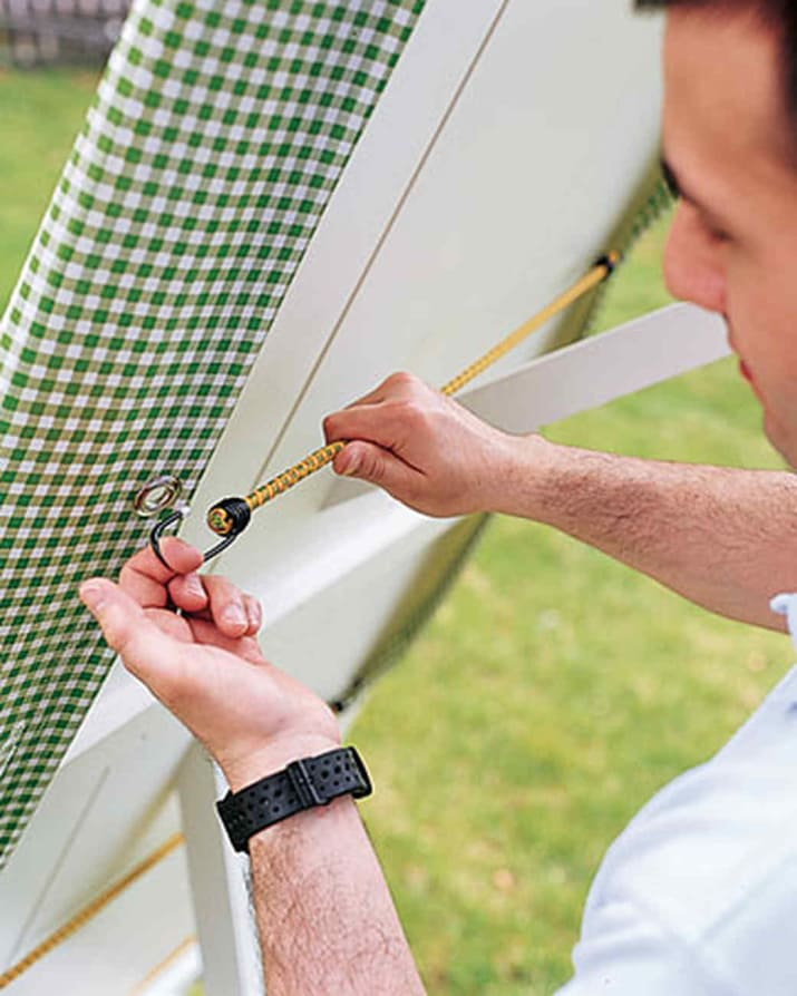 16. Prevent loud tablecloth flapping: hammer in some grommets and anchor with bungee cords.
