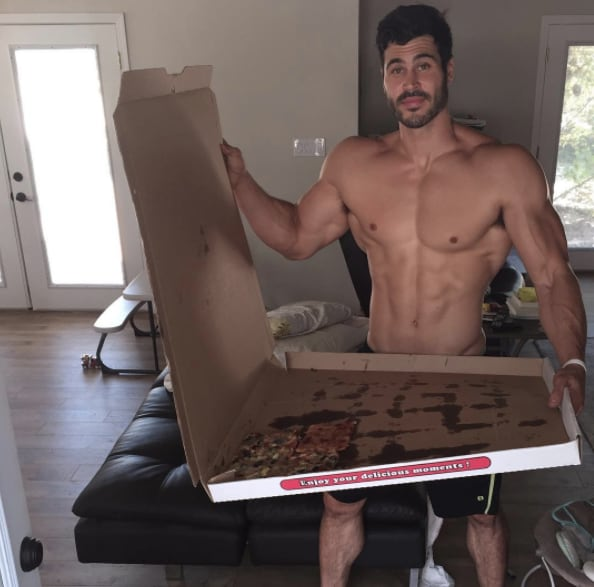 ...and posing with abs with a giant pizza.