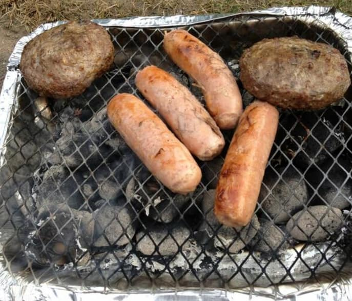 16. Slightly burnt sausages and burgers, prepared on a disposable barbecue.