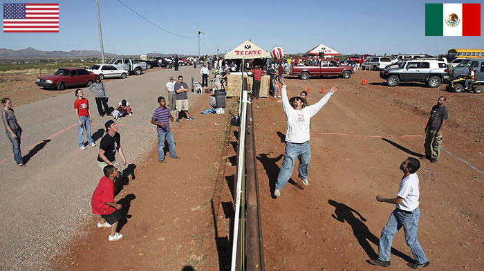 Residents Of Naco, Arizona And Naco, Mexico Play Volleyball Match Over Fence Between USA And Mexico