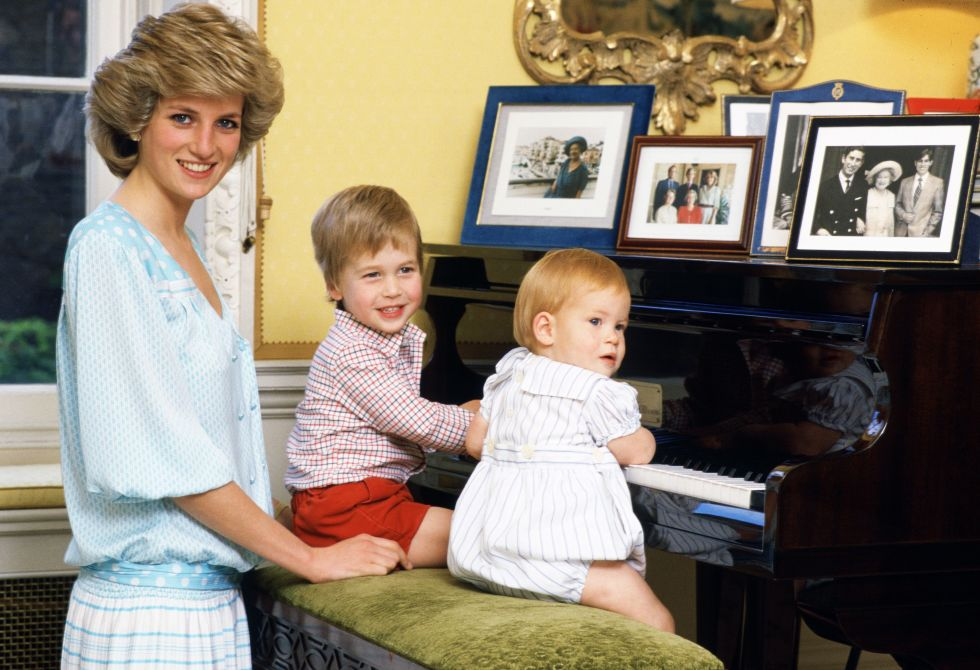 8. October 1985: Playing piano with Prince William and Prince Harry, her sons, in Kensington Palace.