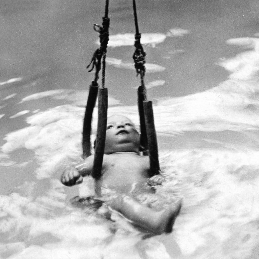13. Using a rope contraption to give infants swimming lessons, 1910: