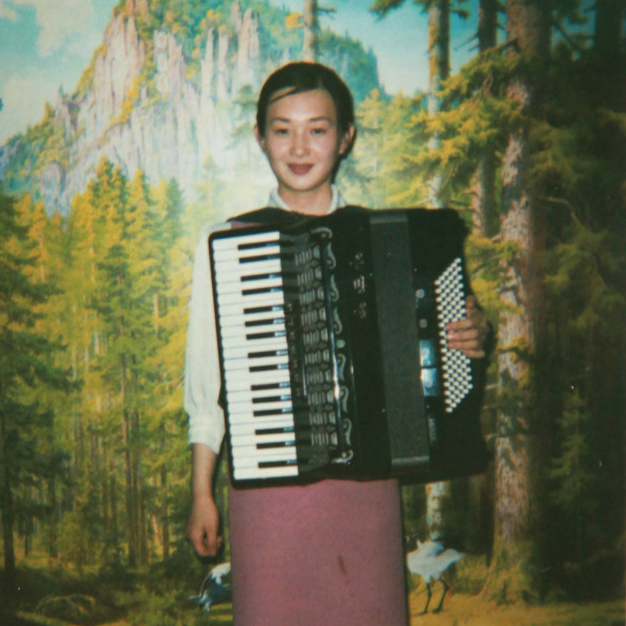 Waitress playing accordion in a restaurant. This is a tradition, once they have finished serving food, they all come to sing. Pyongyang.